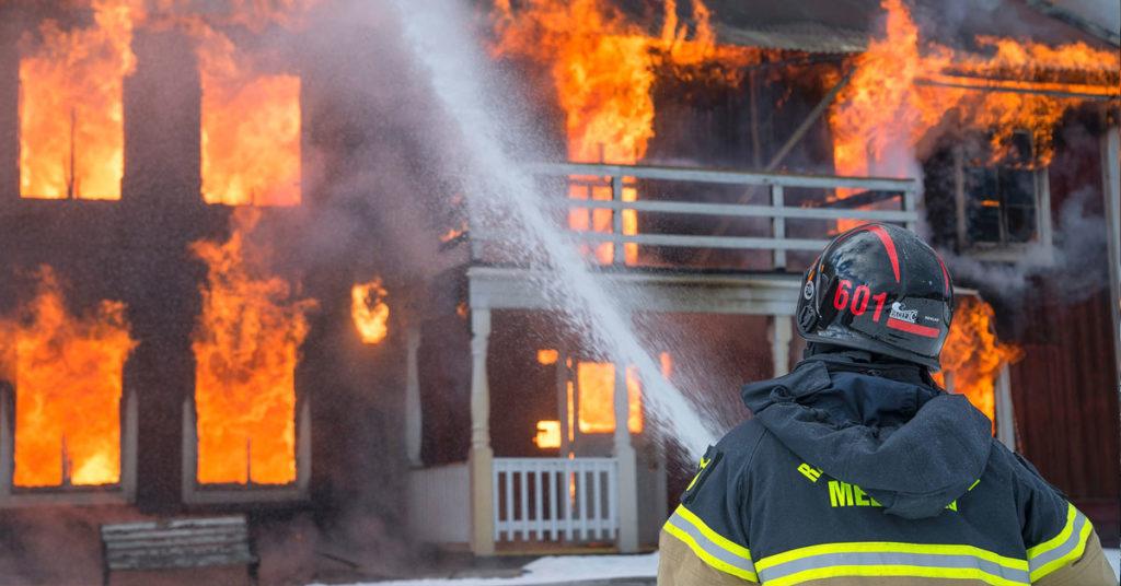 Vigili del fuoco e amianto. Un pompiere in azione su una casa in fiamme.