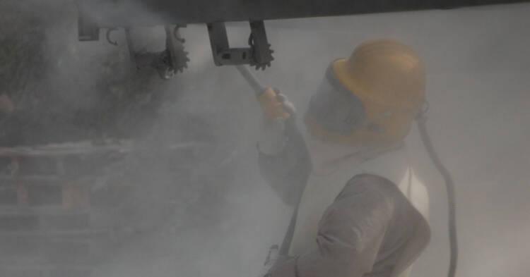 Operaio che effettua la sabbiatura