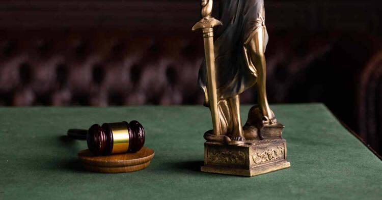 martelletto di tribunale e statua della giustizia
